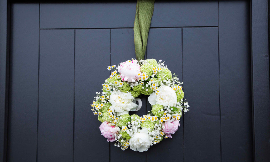 door wreath on wedding day of white and pink roses, matricaria and gypsophila