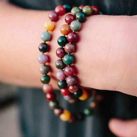 A close up of a therapeutic gemstone necklace around a woman's wrist.