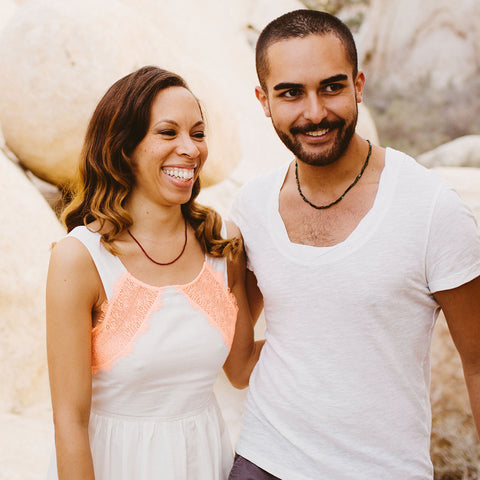 A couple wearing therapeutic gemstone necklaces.
