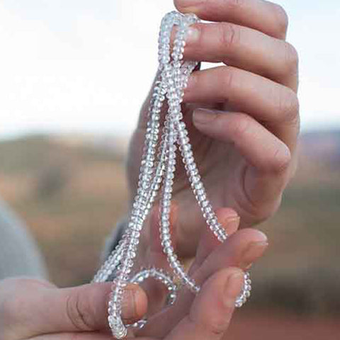 Close up of a white therapeutic gemstone necklace in a woman's hand.