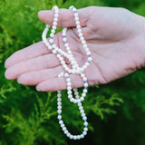 White angelfire gemstone necklace held in a person's palm.