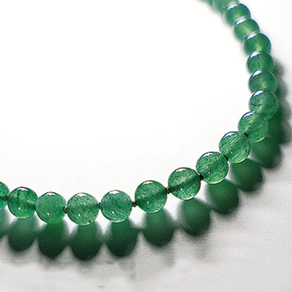 Light green aventurine therapeutic gemstone necklace displayed on a white table.