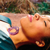 Amethyst necklace coiled up on a woman's neck who is resting on the ground.