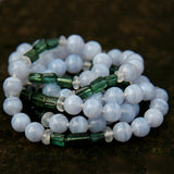 White and green athena gemstone necklace displayed on a black table.