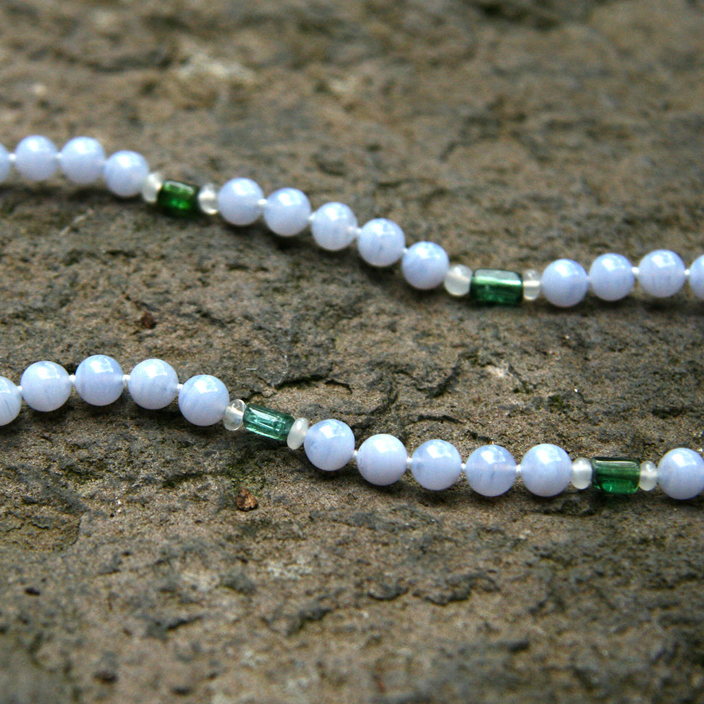 White athena gemstone necklace displayed on a rock.