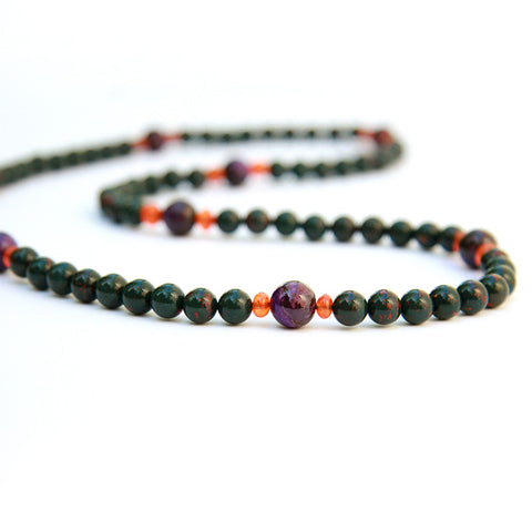 Green and red blood tonic gemstone necklace on a white display table.