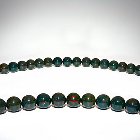 Green bloodstone gemstone necklace on a white display table.
