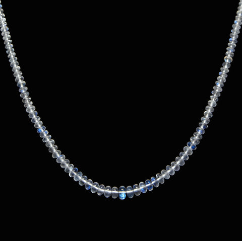 Blue Flash Moonstone therapeutic gemstone necklace being displayed on a black table.