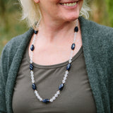 Blue Phoenix gemstone necklace being worn by a older woman.