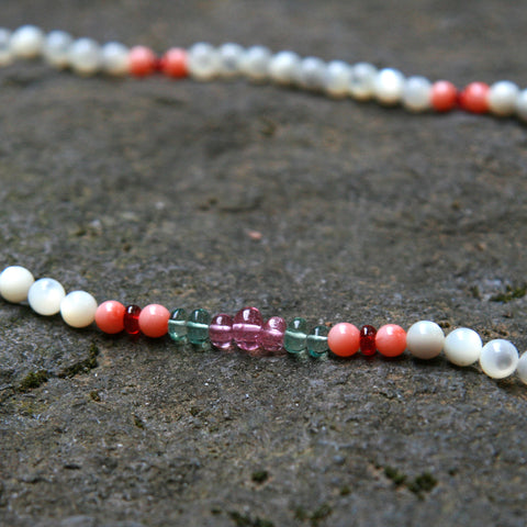 White brigid gemstone necklace being displayed on a rock.