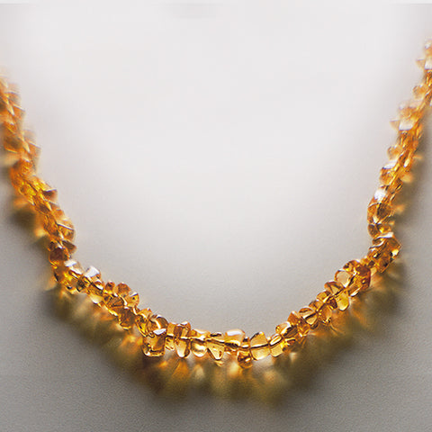 Gold citrine gemstone necklace displayed on white table.