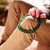 Dark Green Emerine gemstone necklace rested on young man's pant leg.
