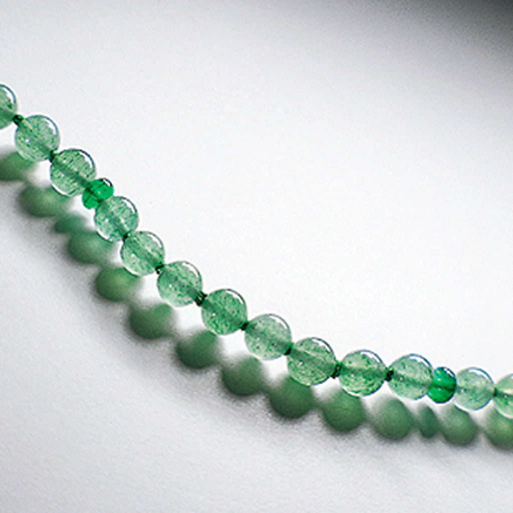 Light green emerine therapeutic gemstone necklace displayed on a white table.