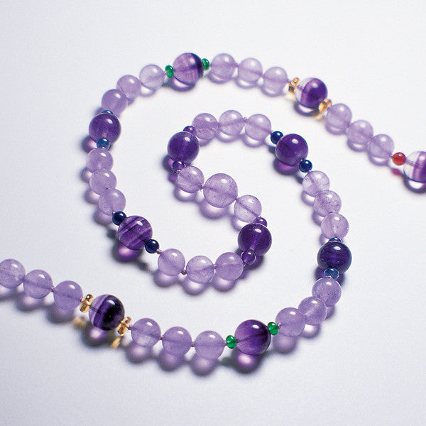 Purple Fluorite Rainbow gemstone necklace being displayed on a white table.