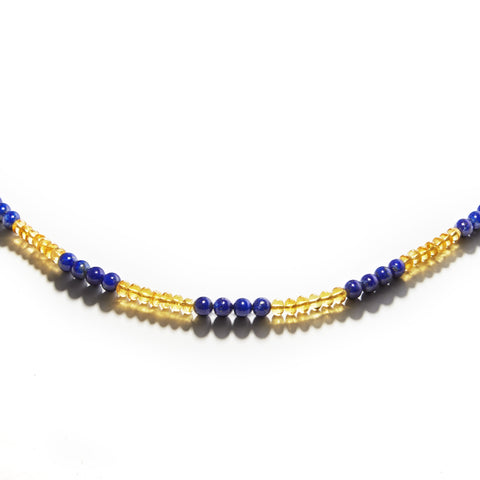Yellow and blue Golden Phoenix gemstone necklace displayed on a white table.