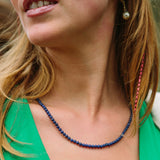 Purple indigo gemstone necklace being worn by a middle-aged woman.