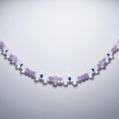 Purple Inner Quest gemstone necklace displayed on white table.