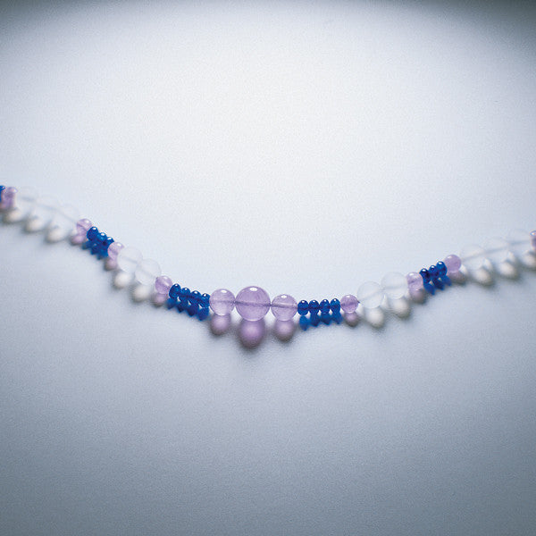Lavender Fire therapeutic gemstone necklace displayed on a white table.