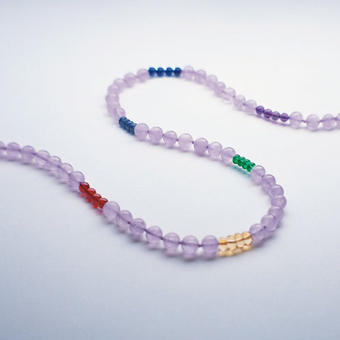Lavender Rainbow therapeutic gemstone necklace displayed on a white table.