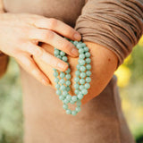 Light green aventurine therapeutic gemstone necklace being held on the arm of a young woman.