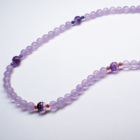 Purple Light Stream therapeutic gemstone necklace being displayed on a white table.