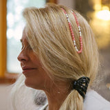 Magic Gift Rhodochrostie therapeutic gemstone necklace being worn by a woman in her hair.