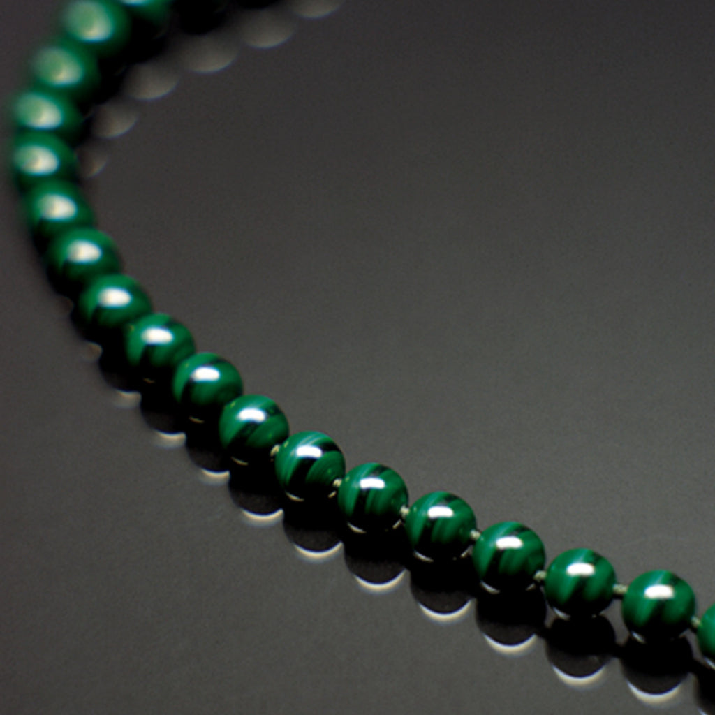 Malachite therapeutic gemstone necklace displayed on a black table
