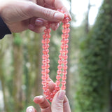 Red rhodochrosite therapeutic gemstone necklace being held in a woman's hands.