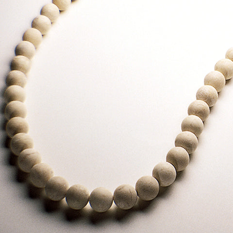 Tan riverstone therapeutic gemstone necklace displayed on a white table.