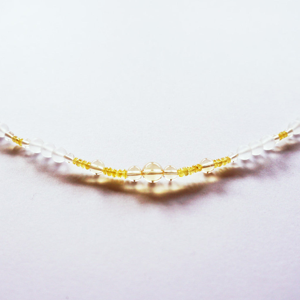 Solar light therapeutic gemstone necklace displayed on a white table.