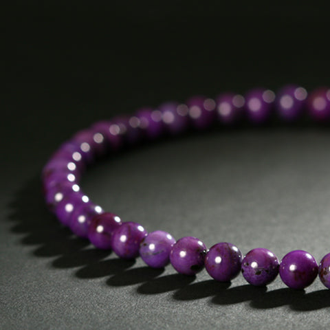 Purple Sugilite gemstone necklace displayed on black and gray display table.