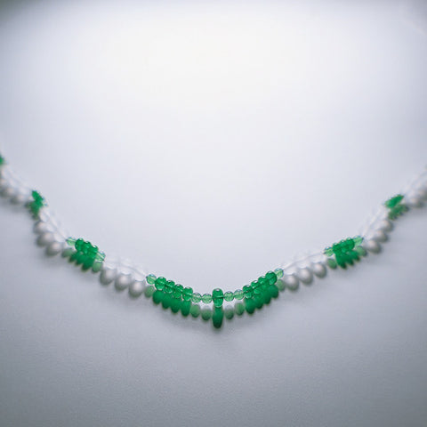 Green and white Summer gemstone necklace being displayed on a white table.