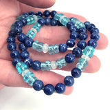 Blue apatite gemstone necklace held in person's hand.