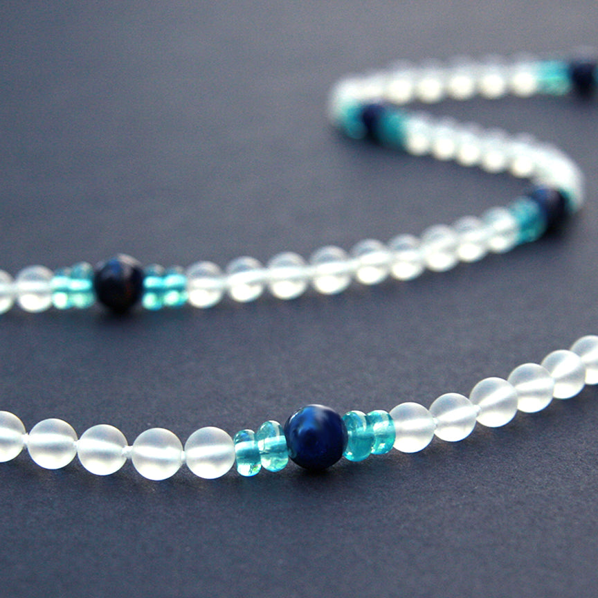 White apatite gemstone necklace on display table.
