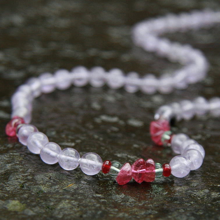 White and red Hearts Wisdom gemstone necklace resting on a stone.
