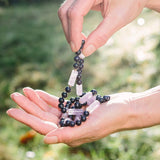 Lavender Light therapeutic gemstone necklace being held in a woman's hand.