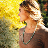 Light green aventurine therapeutic gemstone necklace being worn around the neck of a young woman.