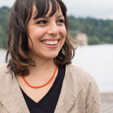 Orange carnelian gemstone necklace being worn by a young woman.