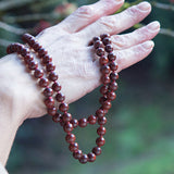 Brown and red poppy jasper therapeutic gemstone necklace being held by an older woman.
