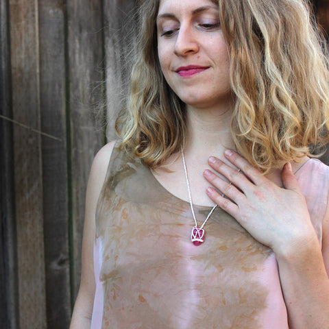 Pink Tourmaline Stone therapeutic gemstone necklace being worn around the neck of a young woman.