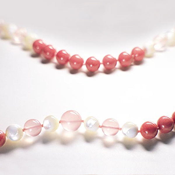 Red and white Radiant Heart therapeutic gemstone necklace displayed on a white table.