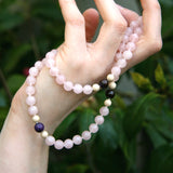 Pink and black Rose Flame therapeutic gemstone necklace being held in a woman's hands.