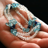 Blue and white Star Aqua gemstone necklace being held in a woman's hand.