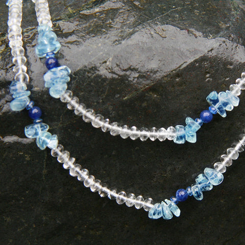 Blue and white Star Aqua gemstone necklace displayed on a black rock.