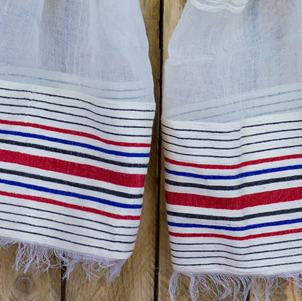 Close up of red and blue stripes on bottom of translucent white scarf.