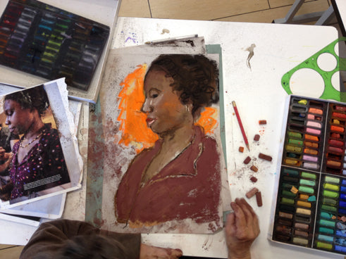 RZ working on a pastel portrait of a woman looking downward. Community Access Art Collective