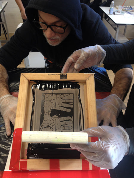 Artist printing a screen print image.