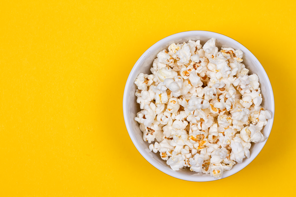 take yourself to the movies, popcorn in a bucket against a yellow background