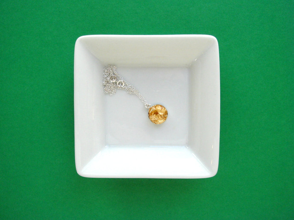 gold necklace in a dish