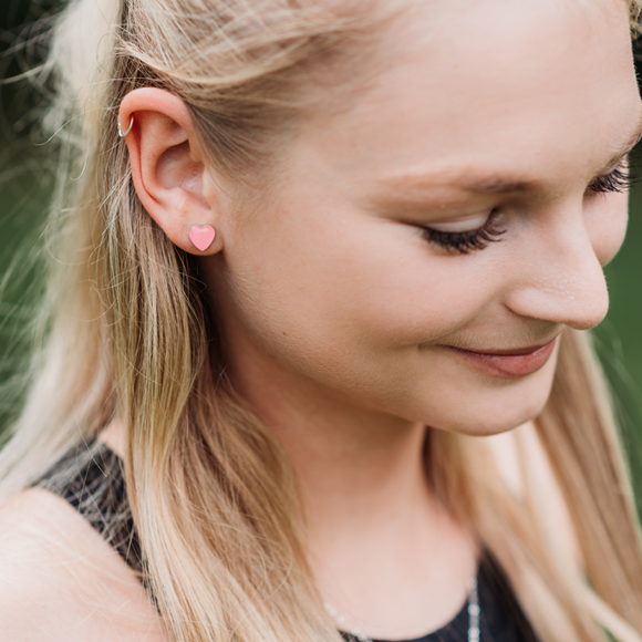 a model wearing small sterling silver heart stud earrings by Kate and Moose